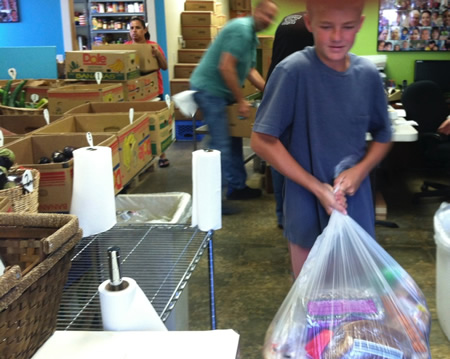 Volunteer Owen McMurray brings in donations for sorting into Laguna's Food Pantry, where people shopping to feed 146 people stopped for provisions the Friday before Christmas, a new one-day record.