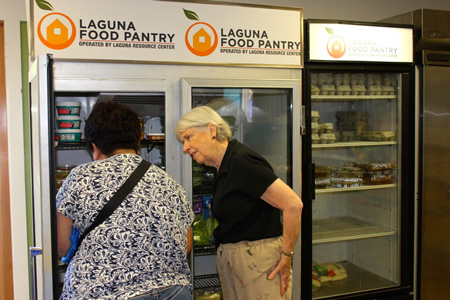 Volunteer and board member Marianna Hof assists shoppers as they procure groceries for their families