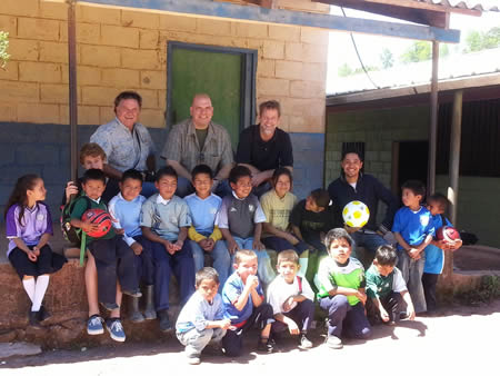 From left, Dave Day, founder of Growers First, Andrew Vournas of Westlake Village's Vournas Coffee Trading and Laguna's Kirk Saunders with school students in El Socorro, Honduras, outfitted for the pitch.