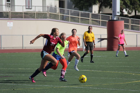 Christa French, 2010 LBHS alumni, sprints past current varsity players Greer Jacobs and Christene Johnson in the annual girls soccer alumni match played on Jan. 4 at Guyer Field. Alumni won 2-0.