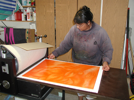 Artist Vinita Voogd creates her work on a printing press.