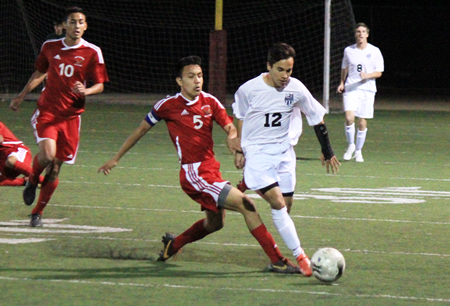 Senior Chris Tellez dribbles the ball around an Estancia defender during Laguna's 1-0 home loss on Friday, Jan. 17.