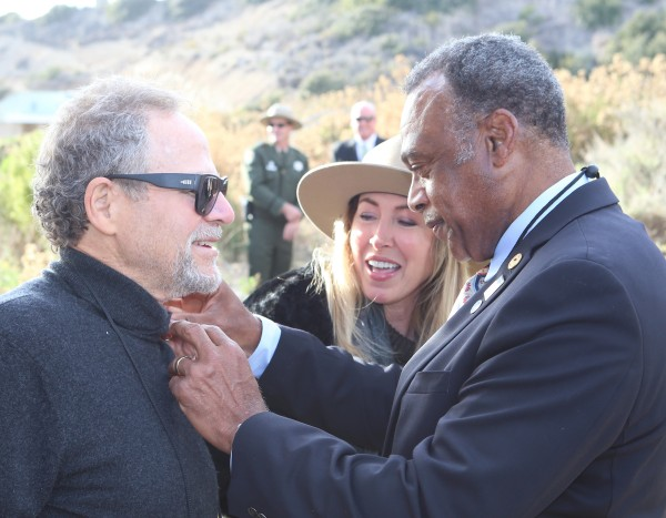 State Parks Director Anthony Jackson fastens the department's 150th anniversary pin on Michael Berns, who with his wife Tricia, last Friday marked the opening of the Berns Environmental Study Loop in Crystal Cove State Park. Photo by Jim Collins