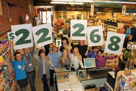 Customer service team leader Milton Chavez, left, and some of his team display the amount raised in cash and food donations for the Laguna Food Pantry by Whole Foods Market Laguna Beach.