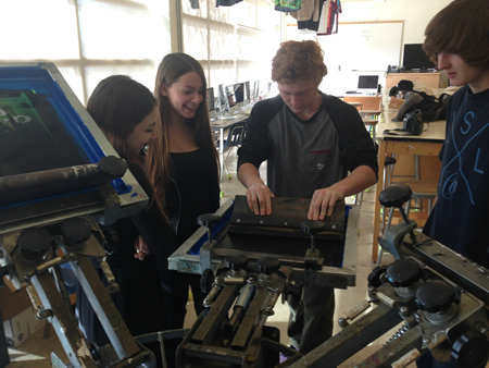 Maria Badagliacco, Elise Waldow, Nolan Campbell and Jake Tidd, from left, learning how to silkscreen in ROP multimedia design class at Laguna Beach High School.