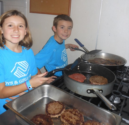 Club members Gabrielle F. and Jackson K. volunteer to prepare a meal for Friendship Shelter residents.