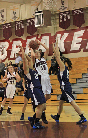 Sophomore Jackie Cenan splits two defenders on her way to the basket during Laguna's 60-28 thrashing of Calvary Chapel at Dugger Gym on senior night, Monday, Feb. 10.