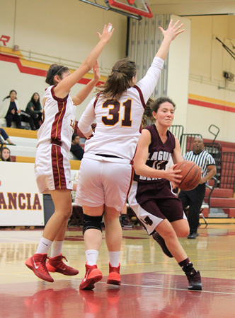 : Sophomore Jackie Cenan drives around two Estancia defenders on her way to two of her game high 15 points in Laguna's 51-37 road loss on Thursday, Jan. 30.