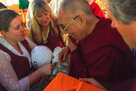 Morgan Lamb, left, and Susan Brown Madorsky ask the Dalai Lama to sign a soccer ball for a sports complex funded partly by donations from Laguna Beach.