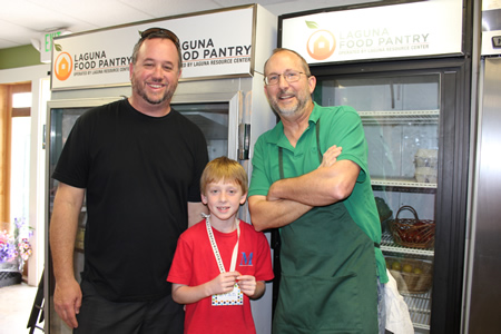 McDowell School first-grader Evan and his dad Sean Cook, left, chatted with Laguna Food Pantry volunteer and board member John Kirtz.