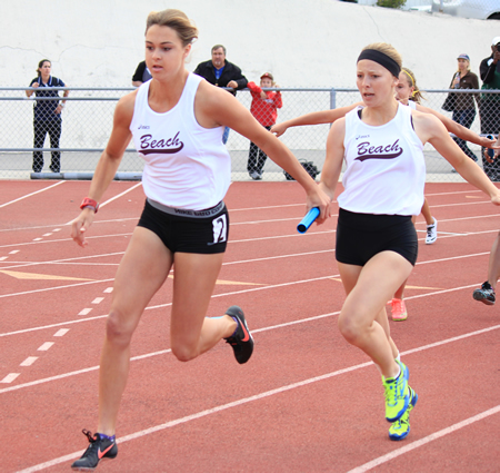 Laguna's Rose Niermeijer passes the baton to Coco Putnam for the final leg of the 4x100 relay.
