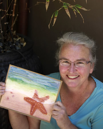 Artist Mary Hurlbut shows off a work from the sea lion painting workshop.