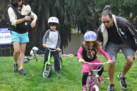 Mitzi Ostrick gets a push from dad, Marc, while Grayson Grzeskowiak waits for help from Megan Hilliard at bike riding clinic. Photo by Michelle