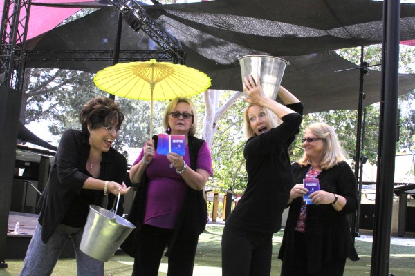 "Healthy Girls Festival organizers, from left, Connie Burlin, Mary Schmidt, Maggie Hempen and Mary Sausen clown around with water-filled buckets and passports.  The event allows girls to ""tour"" the globe and experience their peers' chores, like lugging water."