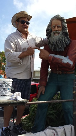 Artist Mike Tauber restores the Brooks Street Greeter sculpture of Eiler Larsen in 2014.