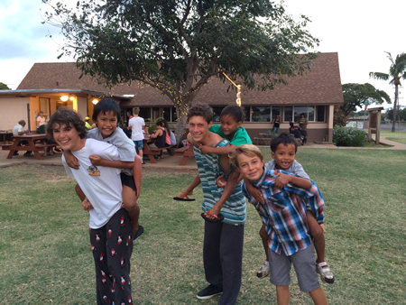 From left, Zane Herr, Jake Onodera, and Connor Brashier play with local children of Molokai.