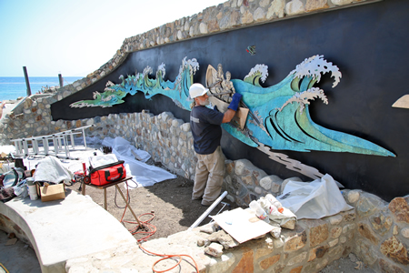 Metal sculptor Terry Thornsley installs the centerpiece of a just completed mural outside Main Beach's lifeguard headquarters. A official dedication is expected soon.  Photo by Jody Tiongco