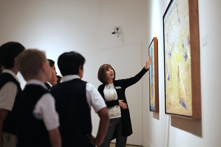 A museum docent explains one of the art work's to a visiting school group.
