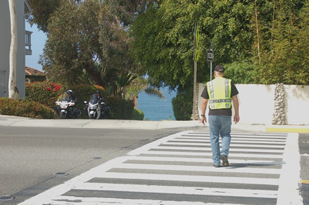 Motor officers keep an eye out for scofflaws who ignore pedestrians in crosswalks at Eagle Rock Way and Coast Highway. Photo by Tom Berndt.