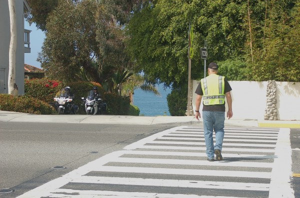 Motor officers keep an eye out for scofflaws who ignore pedestrians in crosswalks at Eagle Rock Way and Coast Highway. Photo by Tom Bernt.
