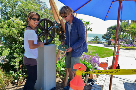 "With Heisler Park's amphitheater as their setting, Scott and Naomi Schoenherr last week assembled their public art installation, ""Time Connected."" Taking as its theme nature's own time clock, the work's cogs and wheels takes inspiration from lunar and tidal cycles and embellishments from handmade ceramics representative of the native marine environment. Photo by Danielle Robbins"