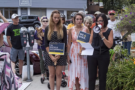 From right, Joan Colvin and her daughters, Natalie and Shayna, express dismay over the city's lack of infrastructure for cyclists at a rally Tuesday. Her husband and their father, John Colvin, died after being struck by a motorist in June. Photo by Mitch Ridder