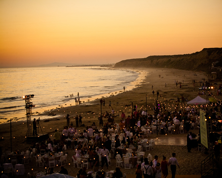 A gala crowd takes in last year's sunset on the sand