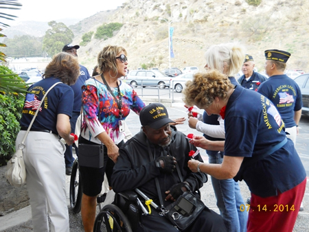 Legion volunteers pin a poppy on a veteran during a visit to the annual tableau vivant production.