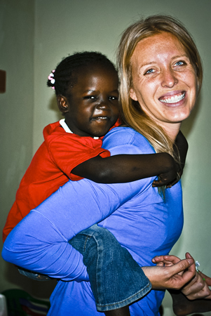 Laguna Beach philanthropist Lindsey Pluimer gives Queen a boost. The child is a resident of St. Ann's Orphanage in Kenya, built with the assistance of a nonprofit Pluimer founded.Photo courtesy of With My Own Two Hands Foundation: