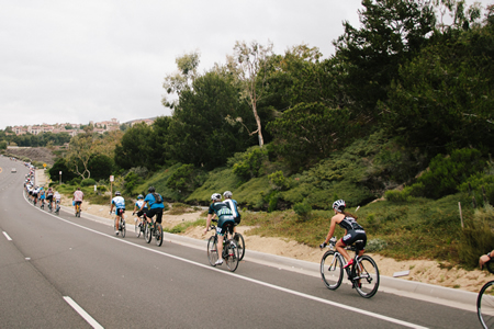 Cyclists on the memorial ride head uphill along the Newport Coast.