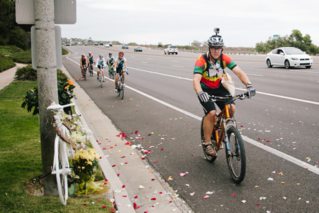 Cyclists toss rose petals near Emerald Bay during a memorial ride Sunday, July 20, to two Coast Highway shrines to bicyclists that died in collisions with cars in the last year.