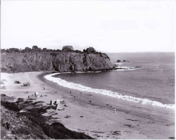 A rare early 1920s image showing the promontory now known as Smithcliffs and Seal Rocks, as seen from Emerald Bay. On the point is the Dobbins' house, Dos Rocas, and behind it the Lowe house, later moved to McKnight Drive. Photo courtesy of First American Title Corporation.