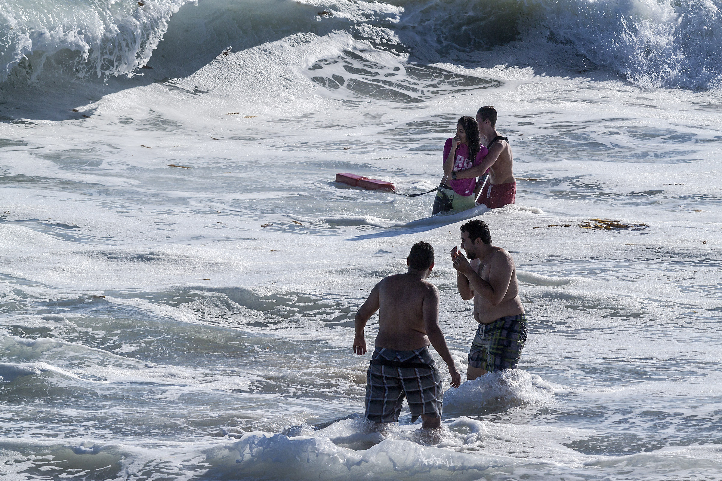 A rookie seasonal guard aids a swimmer in large surf at  Main Beach this weekend. Photo by Mitch Ridder