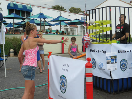 Donations are still being accepted for the Boys and Girls Club, the beneficiary of  a dunk-a-cop fundraising booth set up on Main Beach last Saturday. Besides cops volunteering to get a dunking, so did City Council member Toni Iseman, who is seeking re-election. The police employees association raised $686. At a $1 a throw, a lot of people stopped by. Photo by Darin Germaine.