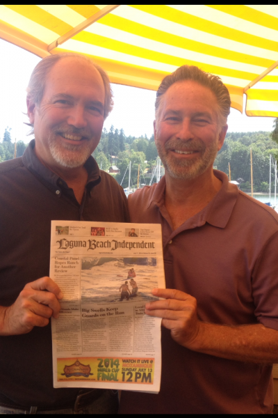 Former Laguna Beach school board member Steve Rabago (left) recently relocated to Bainbridge Island, Wash. Friend Denny Freidenrich visited recently and brought along the hometown read.