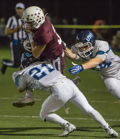 Bruce Knill is upended by University's Matt Abellaneda on a rush around left end.  Knill carried 12  times for total yardage of 34.