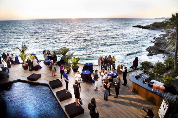 Guests mingle on the oceanfront patio of the Wilson home.