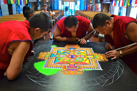 Monks delicately create an intricate temporal sand artwork in the Neighborhood Congregational Church sanctuary during a previous visit.