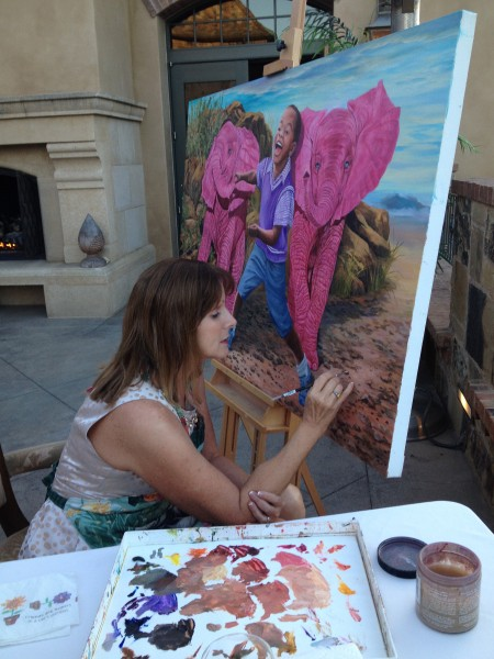 : Laura Curtin paints at the Art-a-Fair, a work she donated to a non-profit in Newport Beach.