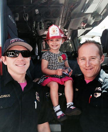 Laguna fire houses opened for public tours last weekend during national fire prevention week. Captain Tom Padden and Engineer Alex Pacheco took time out for visitor Layla Roberson-Beery, 2.