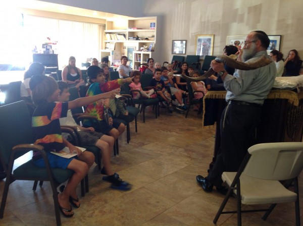 At a high holiday workshop, participants learned the meaning and blessings of the ram's horn from Rabbi Eli Goorevitch.