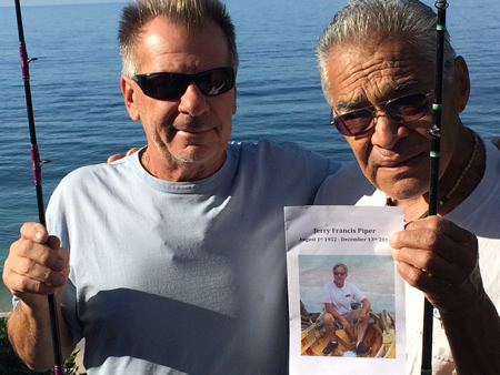 """Steve Battaglia, left, and Alfred """"Dee"""" Devito, holds a program from the memorial of Jerry Piper. The remaining fishing buddies will carry on the annual community fish fry they began together, taking place Saturday at Bluebird Park. Photo by Clay Berryhill."""