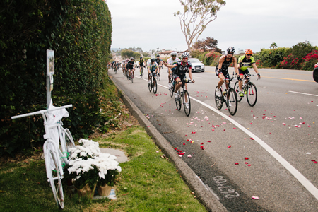Cyclists toss rose petals near Emerald Bay during a memorial ride last July to two Coast Highway shrines to bicyclists that died in collisions with cars over the previous 12 months. Photo by Shayna Colvin