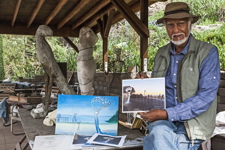 Suki Dail in his outdoor studio with a drawing of the proposed sculpture.