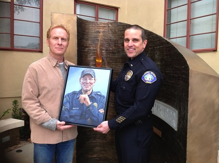 Artist Jorg Dubin, left, and Lt. Jeff Calvert, right, with the artist's portrait of Officer Jon Coutchie near a memorial to him as well as another officer who died while on duty. Photo by Daniella Walsh