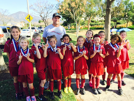 Coach Mike Morgan led the Laguna Beach under 8 all-stars to a hard fought 1-1 draw this past Sunday, Jan. 25, against Mission Viejo, who entered the contest undefeated. From left, Coach Mike Morgan with   Siena Jumani, Tatum Cecil, Kara Carver, Presley Jones, Kayleigh Thomas, Maris Morgan, Isabella (Izzy) Gray, Isabella (Bella) Martino, Natalie Boyd, Aya Hodge and Cate Alexander.