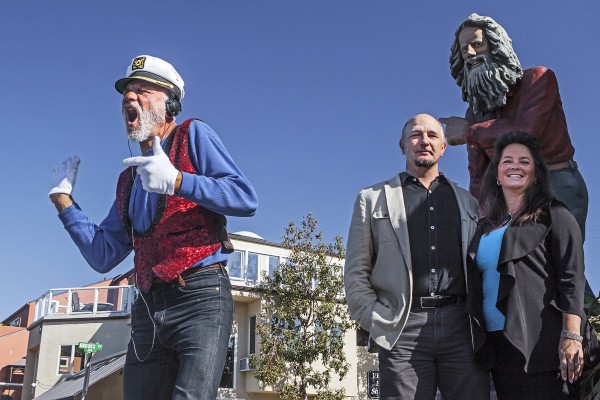 New residents Martin and Tabitha Yewchuk, right, made a film about Laguna Beach's greeters past and present. Michael Minutoli, left, takes up a role inhabited by Eiler Larsen, depicted in a sculpture at Brooks Street and Coast Highway. Photo by mitch Ridder.