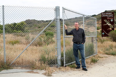 Bob Borthwick identifies a chain link fence at the Dilley Preserve as one of numerous eyesores in his plan to restore the natural beauty of Laguna Canyon Creek and its corridor. Photo by Jody Tiongco.