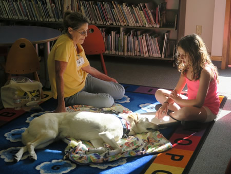 """Shylee Roohian, 10, of Laguna Beach, took part in the Read to A Dog Program  at the Laguna Public Library. """"As you can see, the dog loved it!"""" says photographer Jessica DeStefano."""