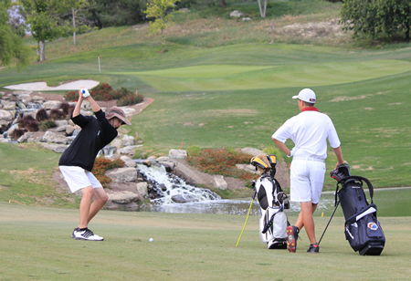 Senior John Grayden watches as freshman Drake Dvorak hit his approach shot on #17 during Laguna's league title clinching victory over Estancia at Aliso Viejo Country Club. Credit: Robert Campbell